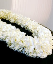 Full and fragrant carnation lei in their natural color.