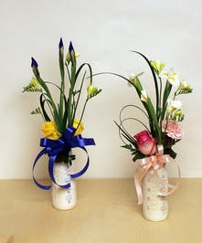 Welcome the new bundle of joy with a baby bottle bouquet of fresh seasonal blooms of iris, freesias and more.  Select from a baby bottle in blue or pink.