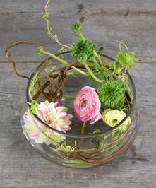 Surprise her with the unexpected to make her blush and feel special.  Fresh cut spring ranunculus with a floating flower candle designed in a glass vase.