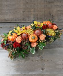 The harvest season is blooming with this harvest design of vibrant golden hues and sunset oranges of roses, orchids, hydrandgea, protea among seasonal foliage, perfect for your table for the autumn season.