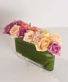 Color Crush is a medley of premium pastel roses designed in a contemporary leaf-lined glass envelop vase.