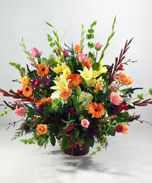 Our Fond Farewell Sympathy Basket is bursting with vibrant colors mixed with whites and accenting greens.