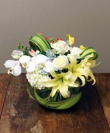 Contemporary composition of orchids, roses, paired with lilies .