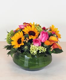 Enchant the summer days with the delicious shades of citrus yellows, oranges and saffron with berry pinks designed in a leaf lined glass vase.