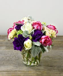 When all of you, love all of thee send a promise of your love.  A collection of luscious roses in blush and vibrant pink garden roses  among seasonal blooms of hydrangea, lisianthus in shades of purple and green are designed in a glass vase.