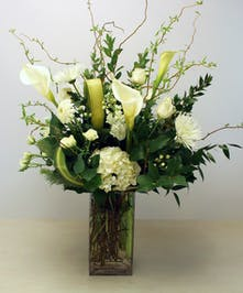 Elegant in shades of ivory and white blossoms of hydrangea, roses, gerbera, lilies, chrysanthemums intertwine with textures of seasonal foliage.  Presented in a glass vase.