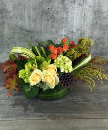 Autumn Chardonnay is a modern twist for the fall harvest celabrations. Blushing with peach roses, hydrangea, cymbidium orchids with accents of spicy orange and fall leaves designed in a leaf lined glass vessel.
