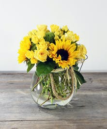 Bring out their inner glow with sunflowers and roses mingle in a rope handle glass lantern.