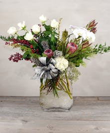 An exquisite snowy white way to celebrate the season with phaleonopsis orchids, fragrant white roses, calla lilies, protea, holiday berries intertwined with pinecones and evergreen designed in a glass vase.